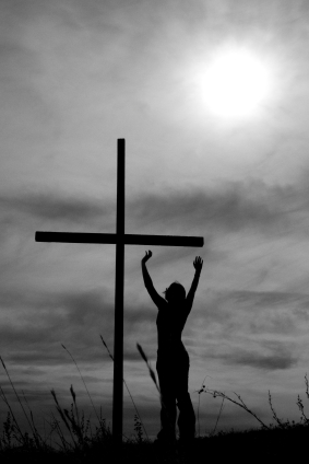 woman raising her arms before a cross