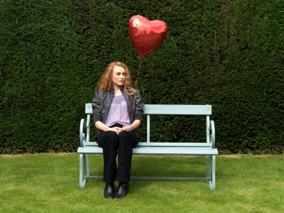 Young girl holding a red heart shaped balloon sits alone on a park bench.